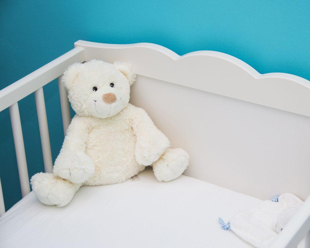 Dziecko - miś siedzący w łóżeczku w środku nocy