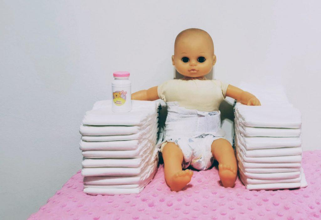 Lalka dziecko siedząca na stosie pieluch