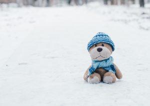 Pies z niebieską czapką i szalikiem na śniegu z niską samooceną