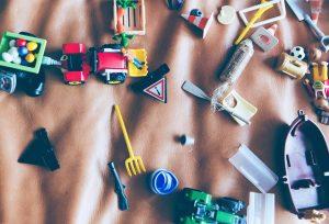 Porozrzucane zabawki na brązowym kocu symbolizujące zabawę dziecka