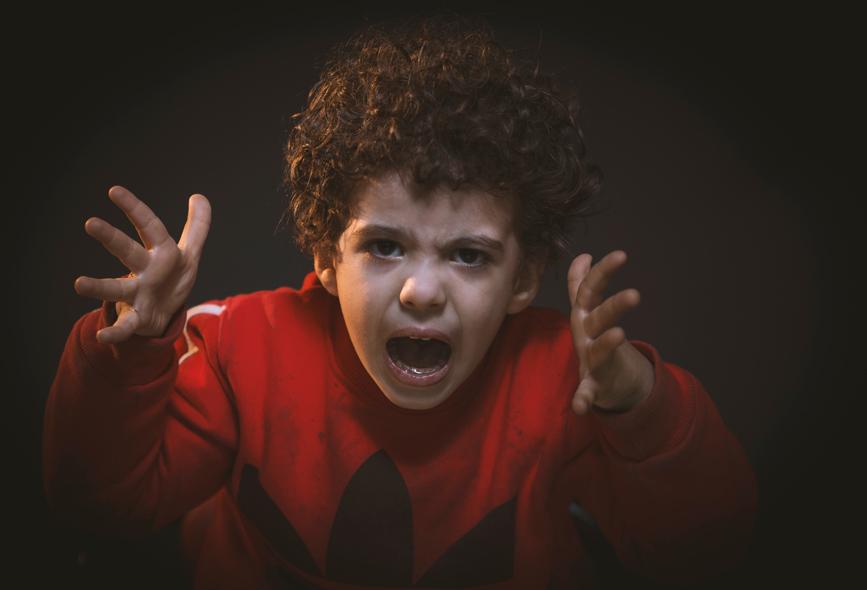 Chłopak ubrany w czerwony sweter histeryzuje
