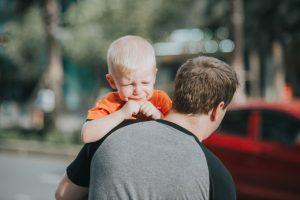 Płaczące dziecko na ramionach ojca