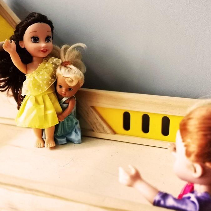 Nieśmiałe dziecko chowa się za mamą, która macha do innej mamy z dzieckiem