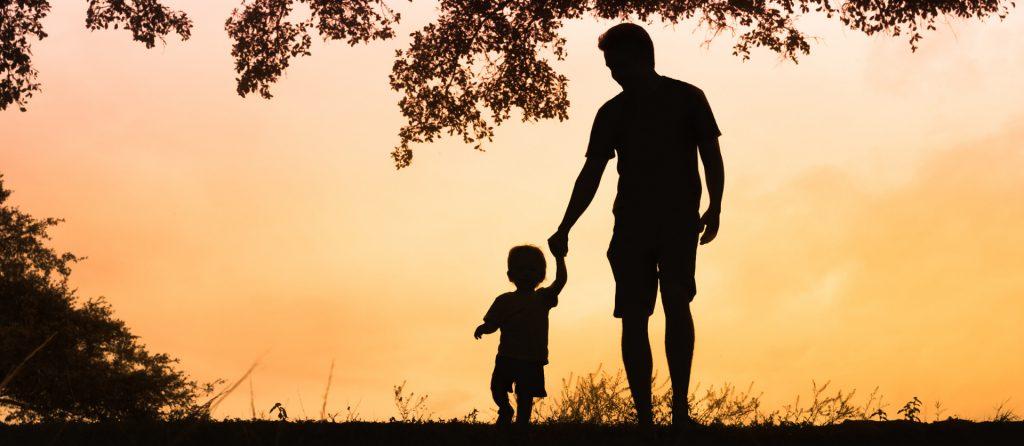 tata prowadzi dziecko za rękę, zachód słońca