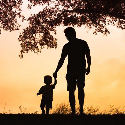 ojciec prowadzi dzięki za rękę przy zachodzie słońca