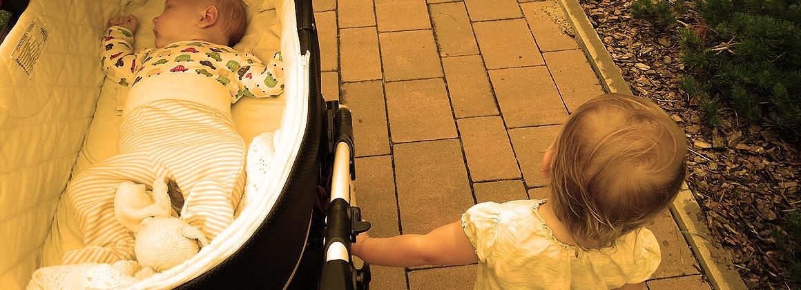 niemowlak w wózku i dwulatek obok na spacerze